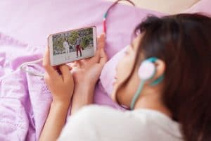 young girl watching mobile video smart phone wear headphones lying on bed